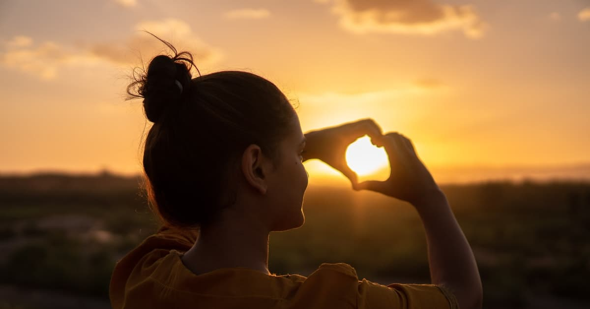 young lady doing heart symbol in sunset